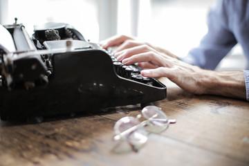 Stylish writer using an old typewriter