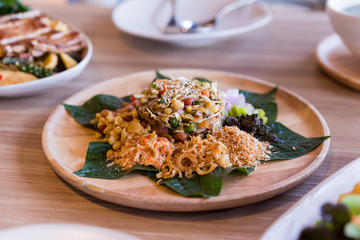 Lahpet is Burmese Tea Leaf Salad served with deep fried garlic, peanut, white sesame, dried shrimp, ginger and roasted coconut.