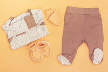 Baby clothes on orange background. Set of clothes newborn, top view