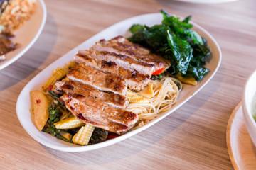 Drunken noodles: Spicy fried egg noodle with basil and pepper served with grilled pork.