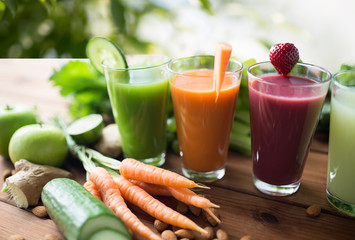 healthy eating, drinks, diet and detox concept - close up of glasses with different fruit or vegetable juices and food on table over green natural background