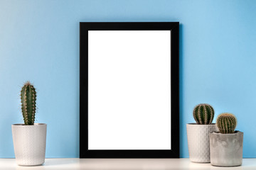 Mockup with a black frame with a white center against the background of a blue wall with three cactuses