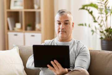 technology, people and lifestyle concept - man with tablet pc computer sitting on sofa at home