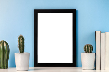Mockup with a black frame with a white center against the background of a blue wall with cactus decoration and books