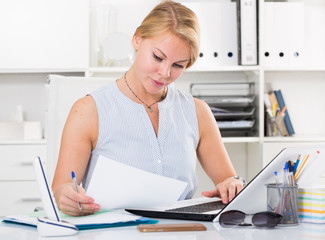 portrait of  business woman  writing and working with laptop in office