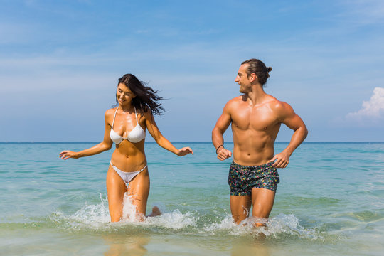 Happy couple laughing together holding hands running having fun splashing water in the ocean waves. Young beautiful fit slim body people enjoying their happy lifestyle in paradise destination beach.