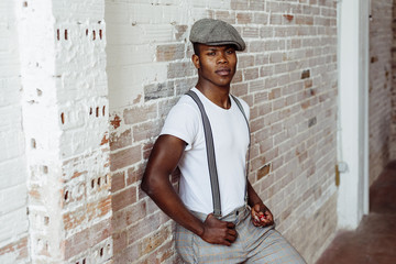 Stylish black man near brick wall