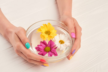 Glass bowl with flowers in female hands. Young woman hands receiving spa treatment. Hands spa therapy.