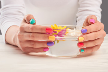 Aroma bath in manicured hands. Young woman hands with multicolored nails holding transparent bowl with water and flowers. Manicure and hands spa.