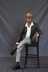 Stylish black man sitting on chair