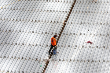A construction worker carries buckets across a sheet metal roof during very hot weather in the Harlem section of Manhattan in New York City