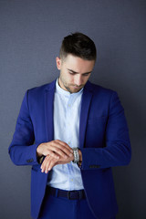 Young business man looking at watch over grey background