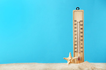 Wooden thermometer with starfish on blue background