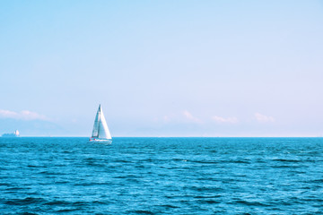 Lonely sailing boat with white sails in open sea. Beautiful romantic landscape, seascape. Luxury sports and recreation background. Horizontal image with copy space.
