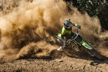 Foto auf Acrylglas Motorsport Motocross rider creates a large cloud of dust and debris