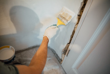 A man's hand with a brush with white door paint. Selected focus