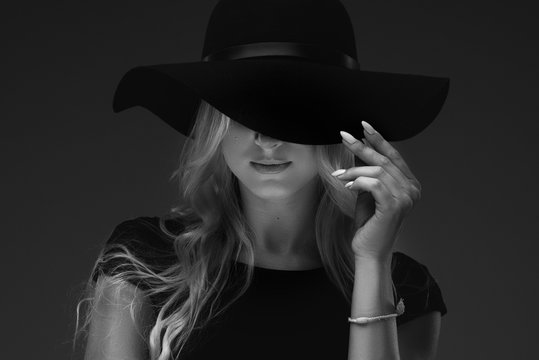 elegant slender girl model in a stylish narrow black dress and a wide hat on a black background. She holds his fingers over his hat, only his lips can be seen