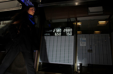A woman walks by an electronic board showing currency exchange rates in Buenos Aires' financial district