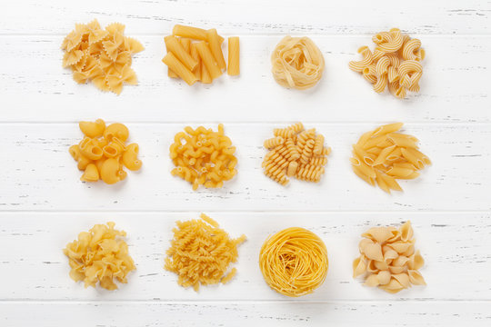 Various pasta on white wooden table