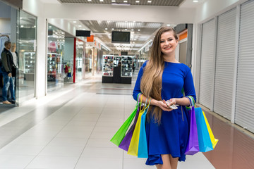 Woman with dollars doing shopping in big mall