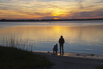 Couple Enjoys the Wonders of Planet Earth As the Sun Sets Over the Bay Behind Them