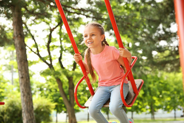 Cute little girl playing on swings in park
