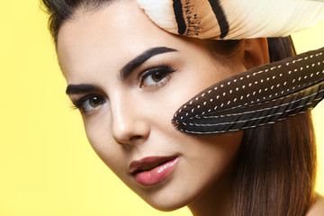 Young woman with beautiful eyebrows and feathers on color background