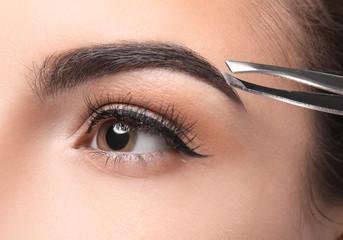 Young woman correcting eyebrow shape, closeup