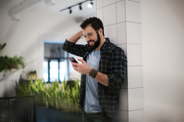 Handsome trendy hipster using mobile phone indoors
