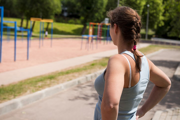 Fit girl on the sports ground with horizontal bars and running tracks