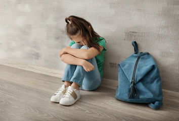 Upset little girl with backpack sitting on floor indoors. Bullying in school