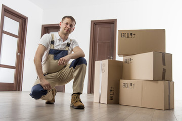 Mover in uniform with cardboard boxes in apartment room of house. Relocation services concept.