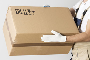 close-up view of cardboard box in mover hands. Relocation services man in uniform with cardboard box.