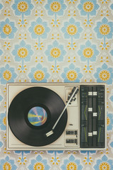 Old record player on top of flower wallpaper