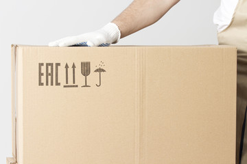 Relocation services concept. close-up view of cardboard box and hand of mover.