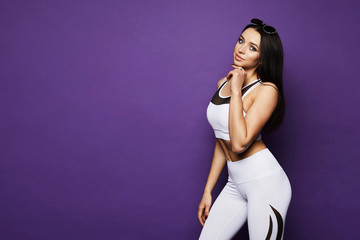 Beautiful and sexy fitness model brunette girl with perfect sporty body, blue eyes and with stylish sunglasses on her head, in white sportswear with geometric patterns pose at violet background