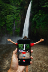 Man taking picture of her girlfriend beside beautiful waterfall