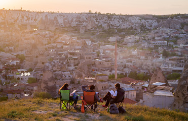 View of Goreme at sunset with the company of students in the foreground, view from the back. Cappadocia, Turkey.