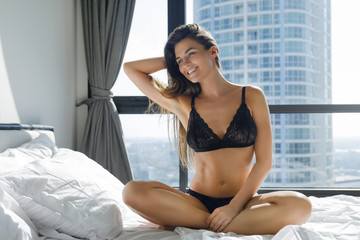 Young and beautiful woman wearing black lingerie sitting on the bed