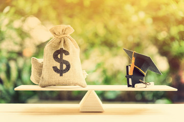 Money cost saving for goal and success in school, education concept : US dollar bills / cash in burlap bags, a black graduation cap or hat, a certificate / diploma and a book on basic balance scale.