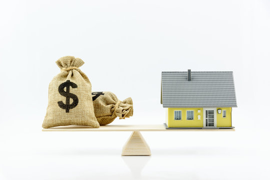 Money saving for home or real estate concept : Dollar or cash in hemp bags or burlap sacks and house on wood balance scale, depicts mortgage loans or buying new asset for investment. White background.
