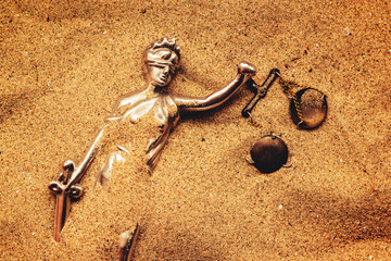 Statue of lady Justice buried in sand