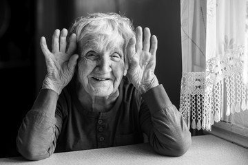 Portrait of cheerful old woman holding wrinkled hands near her ears. Black and white photo. Fototapete