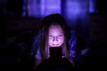 A little girl at night looks at the smartphone under a blanket in her bed.