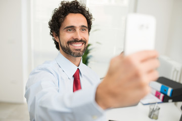 Smiling businessman taking a selfie pic of himself