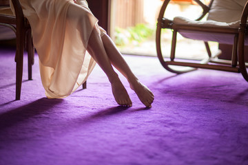 Beautiful young woman's feet close up at home, soft violet carpet floor, can be used as background