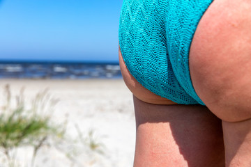 Women's buttocks in a swimwear panties on beach background.Selective focus