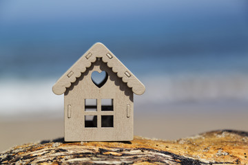 real estate and mortgage invesment . wooden house on the edge of the sea