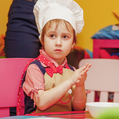 Sweet little cute child girl is ready learn to cook. Humorous photo.