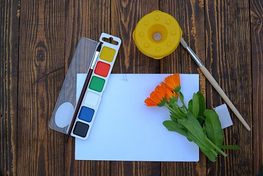 School supplies for drawing lessons on a wooden background. Watercolors, brushes, a glass for water, paper, eraser.  Back to school сoncept.